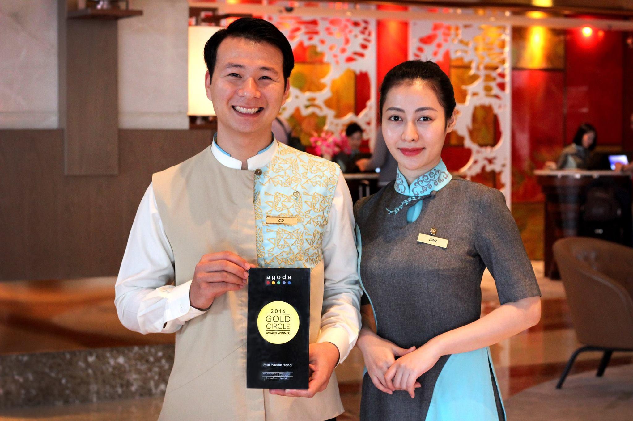 Đồng phục lễ tân màu xanh và ghi kiểu áo dài của khách sạn Pan Pacific Ha Noi