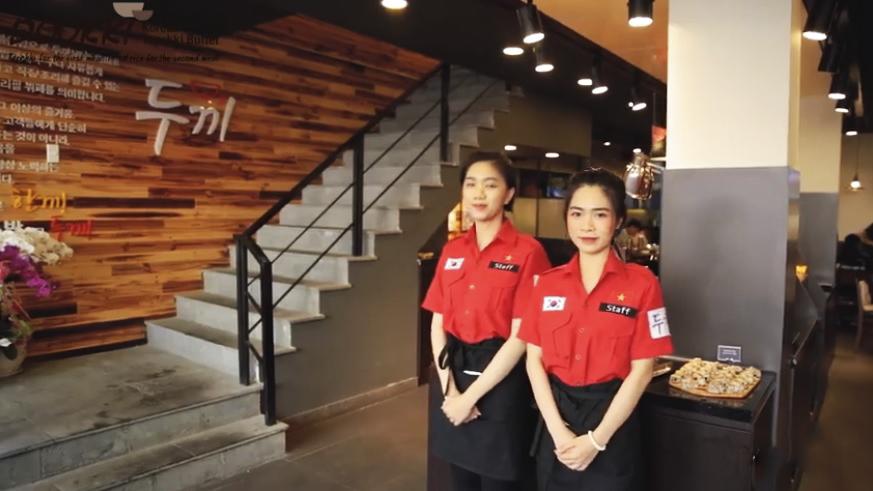 Bộ đồng phục màu đỏ nổi bật của nhân viên nhà hàng Dookki